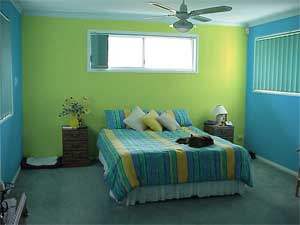 The yellow acts as a feature behind the bed and accentuates the yellow in the bedspread.