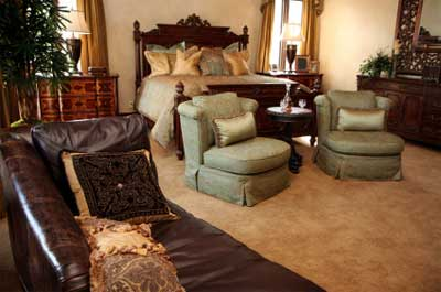 Traditional brown, leather sofas, caramel carpet, and warmed up with peach cushions on the bed!