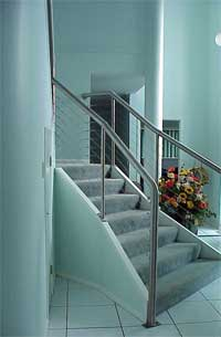 The ceramic tile floor, stainless steel balustrade and handrail, painted walls all create hard surfaces. They are juxtaposed with soft surfaces – carpet on the stair treads and a floral display, balancing the space.